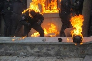 Ukrainian police being attacked by protester's fire bombs.