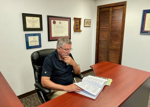 Rod Buckingham sitting at his desk in his Regina office