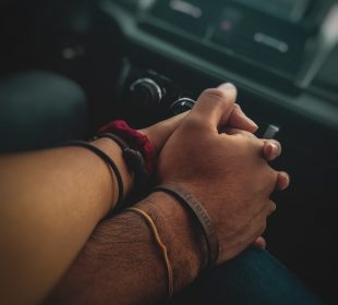 Close up of two individuals holding hands in a car with a blurred stereo in the background
