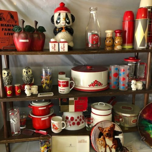 Three shelves with strategically displayed items one could find at the vintage market all following a red and white colour scheme, items such as: metal apples, a panda bear, a bottle, thermoses, owls, salt and pepper shakers, a Campbell's soup mug, some pots and bowls, and a plate with a corgi and a kitten.
