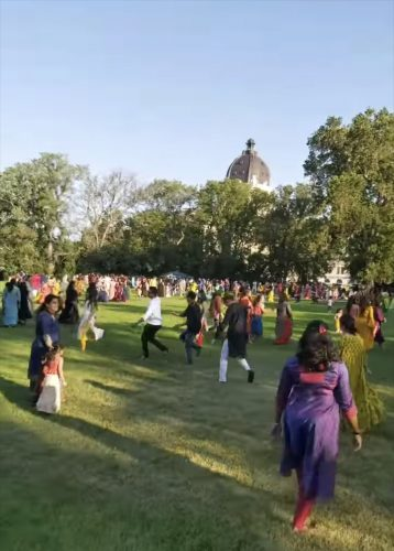 Participants of the Garba-Ras event dance on the greens in front of the Legislative Building.