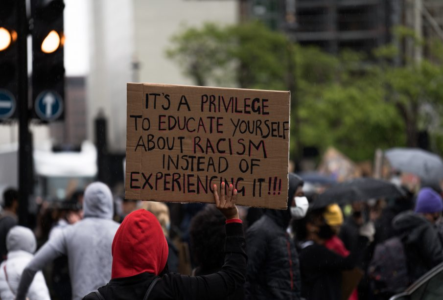 """Black person in red hood holds sign that reads """"It's a privilege to learn about racism instead of experiencing it!!!"""""""