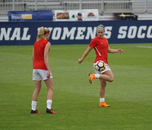 Two women practice soccer on a grass field