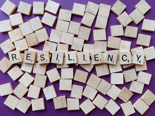 """Scrabble letters spread out to form the word """"resiliency"""""""