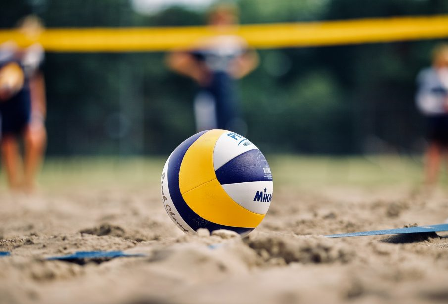 Close up of a blue, yellow, and white volleyball placed in the sand with blurry players and net in the background