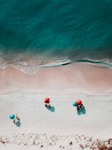 Above view of a beach with umbrellas and a few patrons around the edge of the water