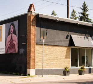 The Slate Art Gallery building from an angle, displaying both the entrance and the billboards for Summer Rhubarb and the next show, Maia Stark's Unwell.