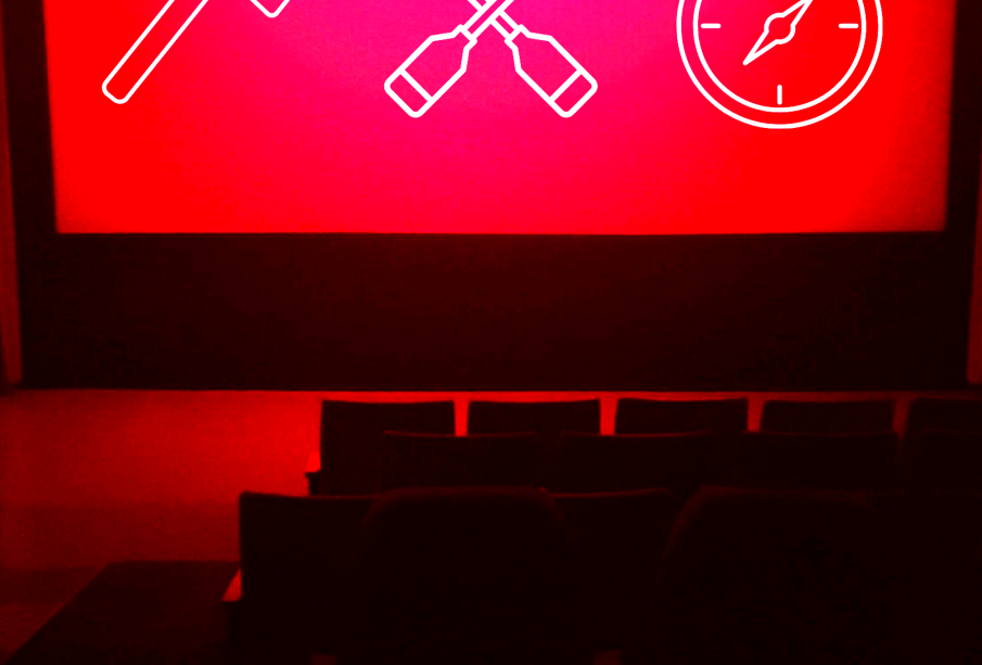 A blank movie theatre screen lit only by red lights shows lineart symbols of an axe, crossed canoe paddles, and a compass in white
